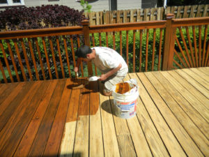 Worker staining a deck